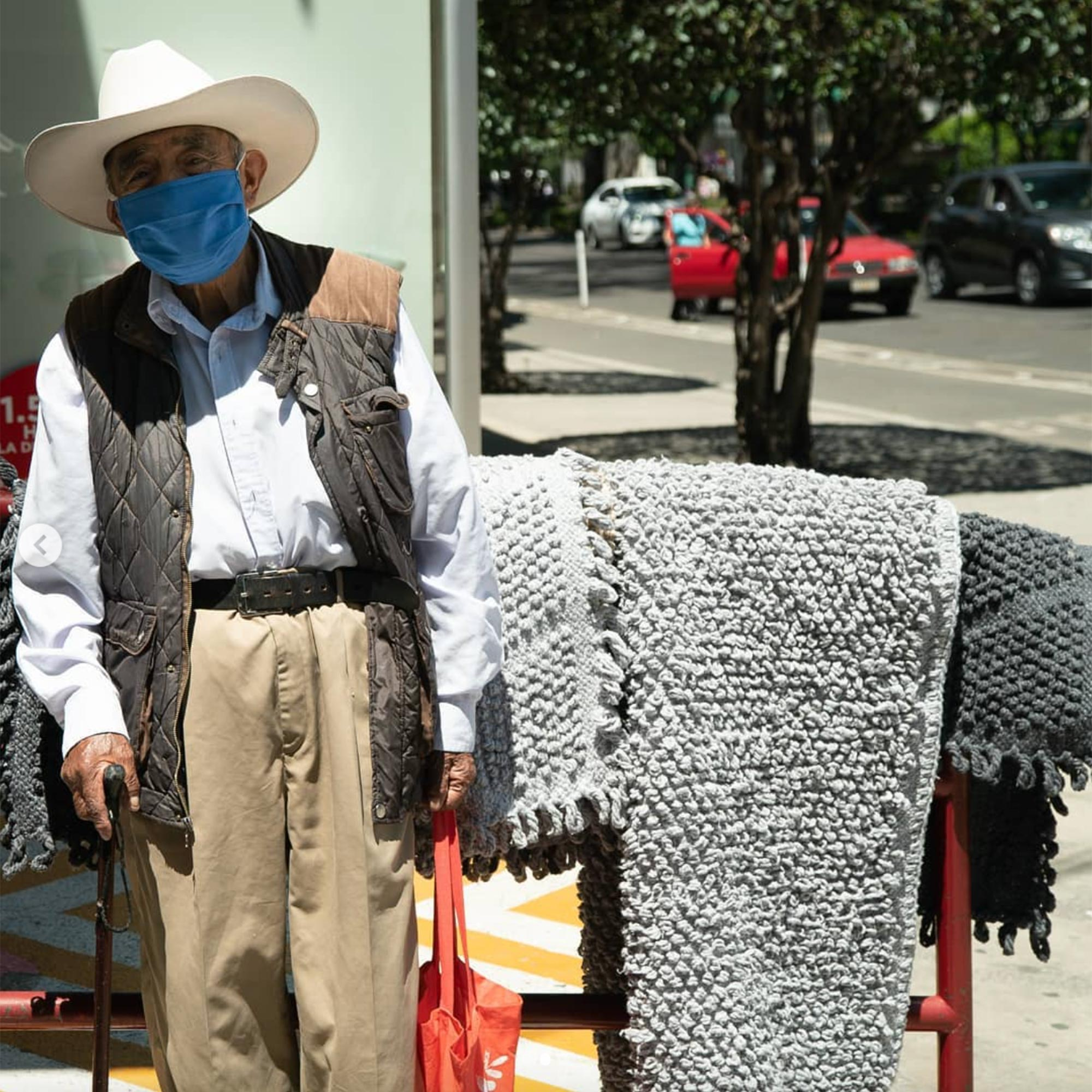 Juan del Río who sells his handmade carpets and rugs on a street corner in Roma neighborhood in Mexico City